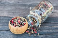 Peppercorn mix in a wooden bowl and glass jar on an old dark wooden table. Colorful peppercorn mix in a wooden bowl and glass jar on an old dark wooden table Stock Images