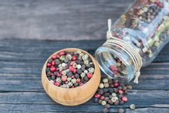 Peppercorn mix in a wooden bowl and glass jar on an old dark wooden table. Colorful peppercorn mix in a wooden bowl and glass jar on an old dark wooden table Stock Image
