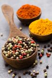 Peppercorn mix in a wooden bowl on grey table. Stock Images