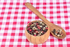 Peppercorn mix in a wooden scoop and wooden bowl on picnic cloth. Colorful peppercorn mix in a wooden scoop and wooden bowl on picnic cloth Royalty Free Stock Image
