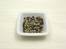Peppercorns on beige underlay. Bowl of chinaware with peppercorns on beige underlay Royalty Free Stock Images