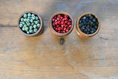 Peppercorns. Green, pink and black peppercorns in wooden glass. Top view Stock Photos