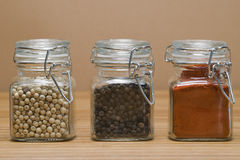 Peppercorns and paprika. Some jars with white pepper, black pepper and paprika stock images