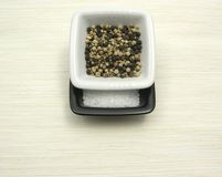 Peppercorns and salt on beige underlay Royalty Free Stock Photos