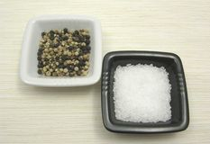 Peppercorns and salt on beige underlay Stock Photo