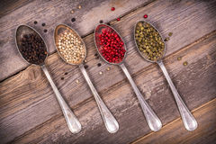 Peppercorns in silver spoons. Tarnished silver spoons containing black, white, pink and green peppercorns over old wood background. Vintage style processing royalty free stock photography