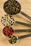 Peppercorns in Spoons Stock Images