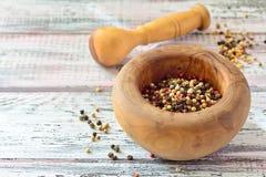 Peppercorns w moździerzu na lekkim drewnianym stole Obraz Stock