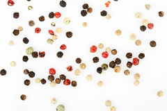 Peppercorns on white. Variety of peppercorns on white surface stock photography