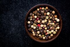 Peppercorns in a wooden bowl Stock Images