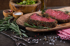 Peppered beef steak with herbs in vintage kitchen Royalty Free Stock Photo