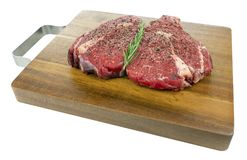 Peppered Raw Rib Eye Steaks on a Wooden Board Isolated royalty free stock photography