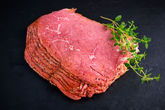 Peppered roast beef pastrami slices on black stone background with herbs Stock Photo