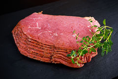 Peppered roast beef pastrami slices on black stone background with herbs Stock Images