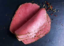 Peppered roast beef pastrami slices on paper with grains of coloured pepper. Stock Image