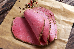 Peppered roast beef slices on paper with grains of coloured pepper. Stock Image