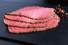 Peppered roast beef slices on stone board with grains of coloured pepper Royalty Free Stock Photos