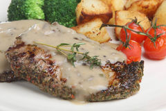 Peppered Steaks with Mushroom Sauce. Peppered sirloin steaks with mushroom sauce, roasted vine-tomatoes and vegetables Royalty Free Stock Image