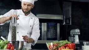 Peppering λαχανικά αρχιμαγείρων σε σε αργή κίνηση Αρχιμάγειρας που μαγειρεύει τα φρέσκα τρόφιμα στην κουζίνα απόθεμα βίντεο