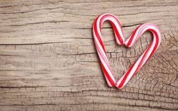 Peppermint Candy Canes in Heart Shape on wooden background. Royalty Free Stock Photo