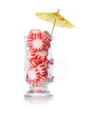Peppermint candy in glass and cocktail umbrella isolated on white. Concept. Red striped mint Christmas candy Royalty Free Stock Images