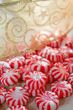 Peppermint Candy and Ribbon. Round peppermint hard candy and gold ribbon with scrolls and stars stock photography