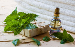 Peppermint essential oil in a glass bottle on a light table. Used in medicine, cosmetics and aromatherapy. White towels, fresh leaves and a piece of soap Royalty Free Stock Image