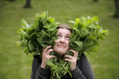Peppermint love. Girl with heart shaped peppermint leaves in hands Stock Photos