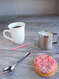Peppermint stick dough nut next  a jug of milk and mug of coffee Royalty Free Stock Photos