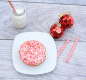 Peppermint stick dough nut next  a jug of milk Stock Photography