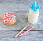 Peppermint stick dough nut next  a jug of milk Stock Photos