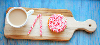 Peppermint stick dough nut next  a and mug of coffee Stock Image