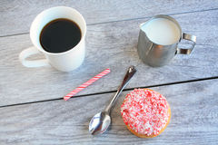 Peppermint stick dough nut next to coffee and a jug of milk Stock Photography