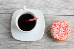 Peppermint stick dough nut next to coffee stick in coffee Stock Photo