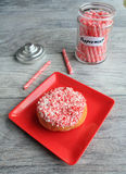 Peppermint stick doughnut next to coffee sticks in jar Royalty Free Stock Photography