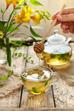 Peppermint tea with honey in glass cup, teapot and flowers Royalty Free Stock Images