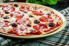 Pepperoni πιτσών με τις ελιές που εξυπηρετούνται Στοκ εικόνα με δικαίωμα ελεύθερης χρήσης