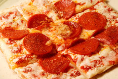 Pepperoni and Cheese Pizza. A personal size pepperoni pizza hot from the oven, sliced, plated and ready to eat Stock Photography
