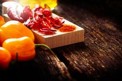 Pepperoni, fresh, dried and ground. On wooden table Royalty Free Stock Images