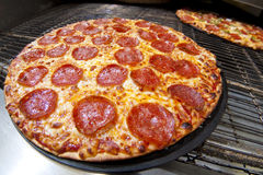 Pepperoni Pizza. Fresh pepperoni pizza coming out of the oven royalty free stock images