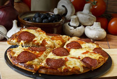 Pepperoni Pizza. Lifted slice of Pepperoni and Cheese Pizza Stock Image