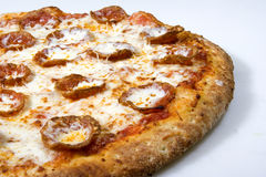 Pepperoni pizza. A closeup of a large pepperoni pizza on a white table Stock Image