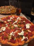Pepperoni Pizza - American style Pizza. Pepperoni is an American variety of salami, made from cured pork and beef mixed together and seasoned with paprika or stock photo