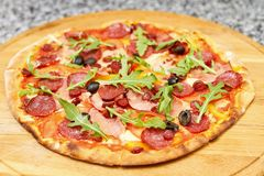 Pepperoni pizza with arugula. Tasty pizza with vegetables and arugula on round wooden board stock photo