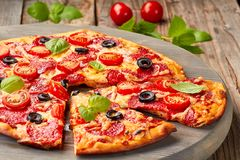 Pepperoni pizza with cherries tomatoes an olives on wooden table. Sliced pepperomi pizza with cherries tomatoes and olives on wooden table. Rustic style royalty free stock photos