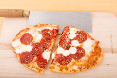 Pepperoni Pizza Cut with Cleaver Royalty Free Stock Photos