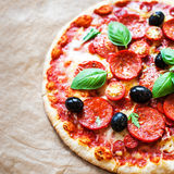 Pepperoni pizza with fresh ingredients on brown baking paper bac. Kground, top view. Banner or wallpaper Royalty Free Stock Photos