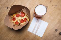 Pepperoni Pizza on Fries and a Beer. Pepperoni pizza on a bed of chips french fries with a beer Stock Photos