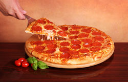 Pepperoni Pizza. Hand taking a slice of Pepperoni Pizza royalty free stock photography