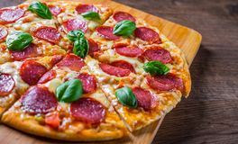 Pepperoni Pizza with Mozzarella cheese, salami, Tomato sauce, pepper, Spices and Fresh basil. Italian pizza on wooden table. Background stock photography